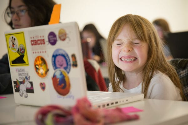 Young girl with laptop smiling at Girls Learning Code summer camp