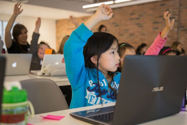 Girls raising hands at Girls Learning Code summer camp