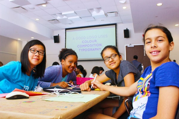 Four preteen girls smiling for camera at Girls Learning Code summer camp