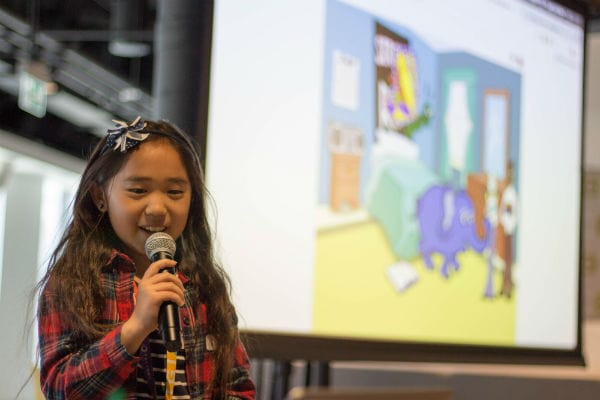 Young girl with microphone presenting in front of projection screen at Girls Learning Code summer camp