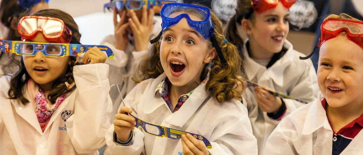 kids in lab coats facing camera amazed by science experiment