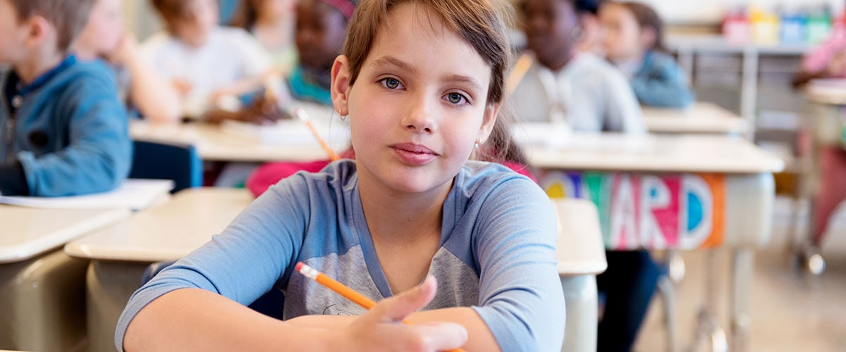 8-year-old student at her desk in school