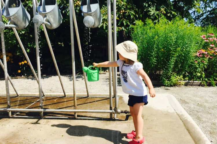 little girl with watering can at waterpark