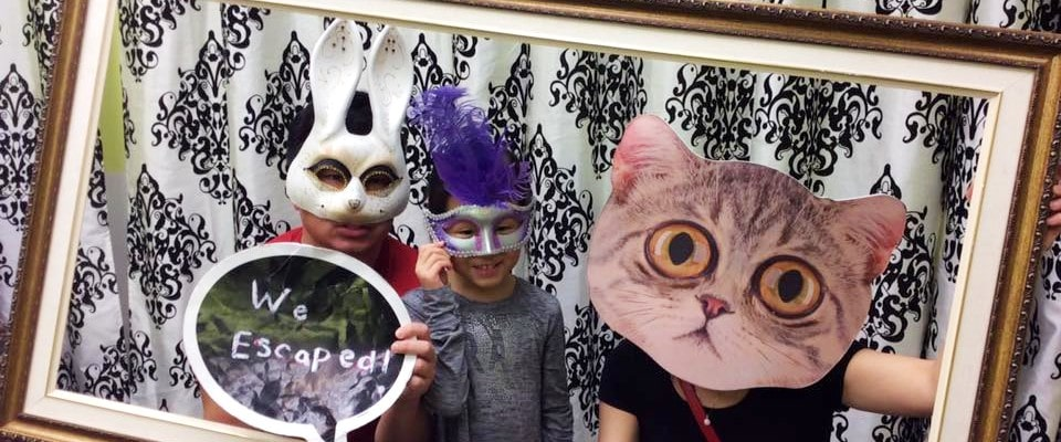 family wearing masks posing for camera at Captive Kids Escape Rooms