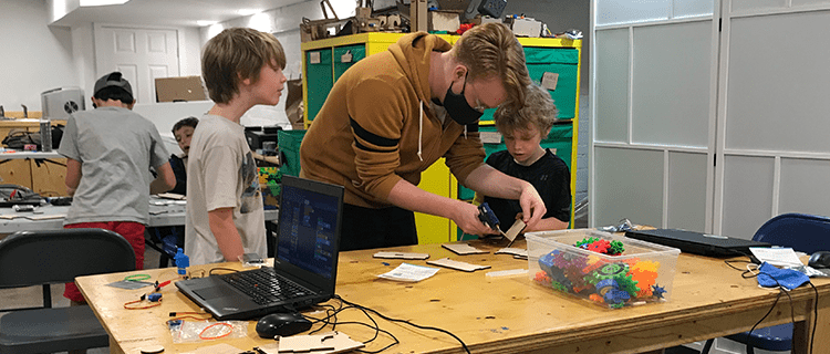 Adult helping kids with hot glue in a Maker Bean class.