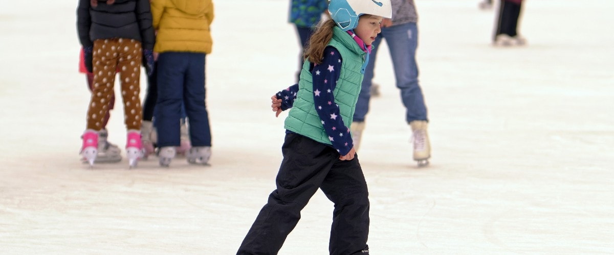 young girl skating on an outdoor ice rink