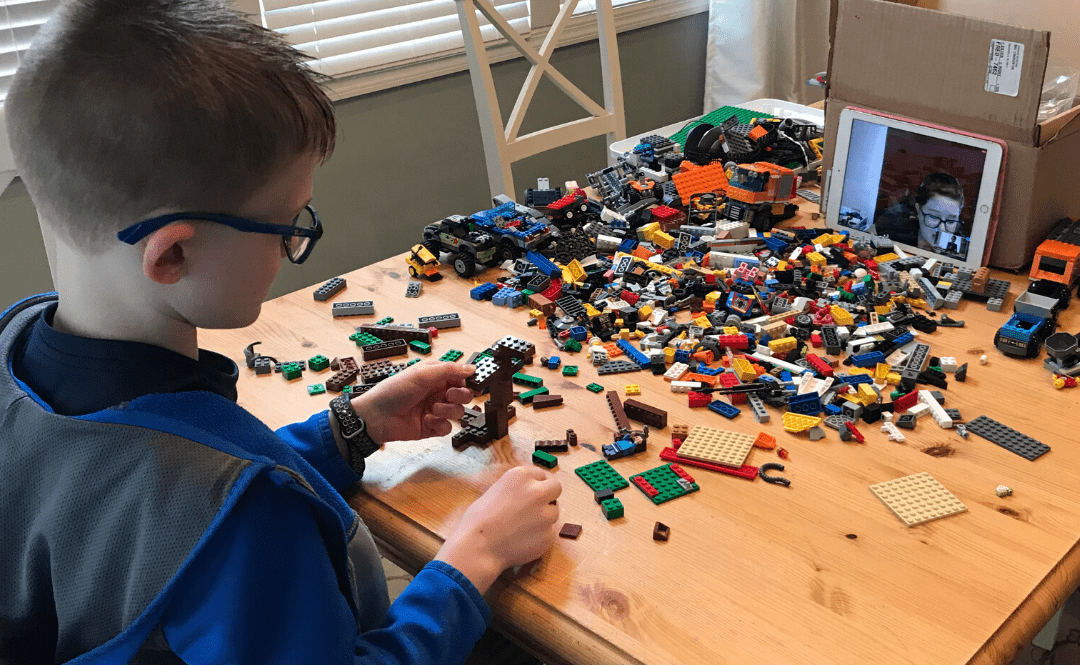 Child building with Lego in front of tablet