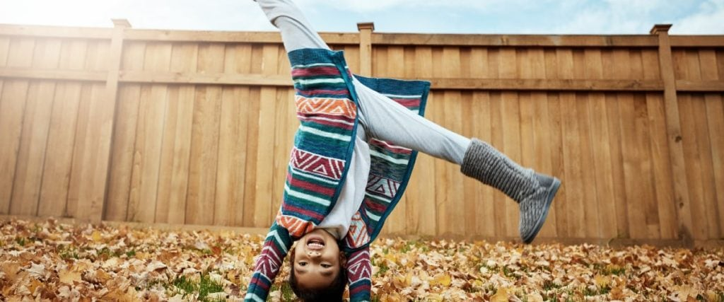 child doing cartwheel in leaves during fall