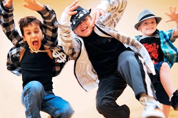 three young boys doing hip-hop moves facing camera