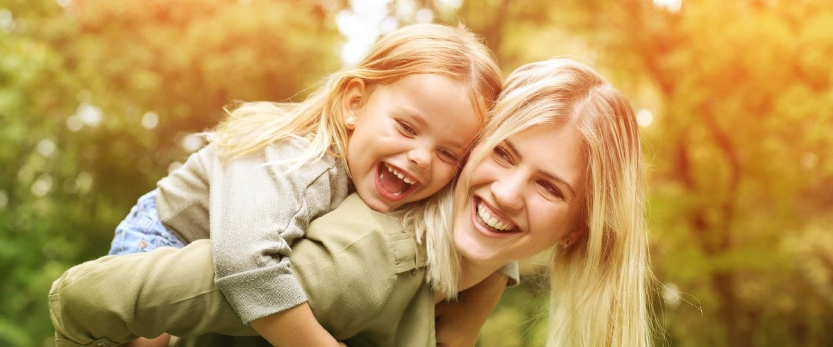 mother giving preschool daughter piggyback ride with fall foliage behind