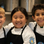 three kids in Rooks to Cooks chef uniforms smiling at camera