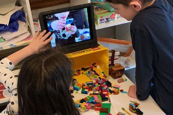 kids building with Lego and watching tablet at virtual Lego party