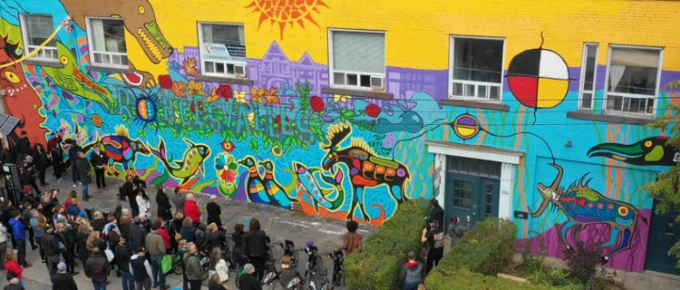 Crowd looks at a building mural on Roncesvalles Avenue.