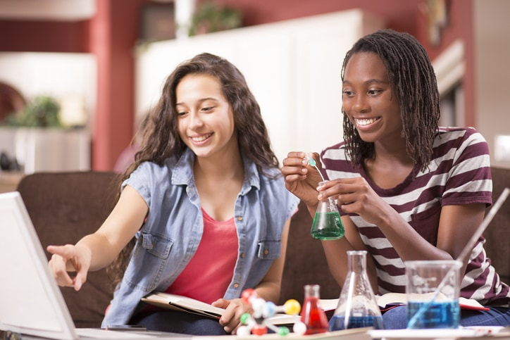 teenage high school girls with chemistry equipment and laptop at home