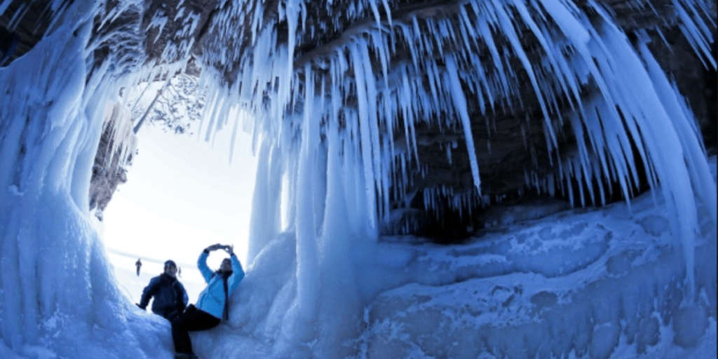 Couple sitting inside an ice cave at Apostle Islands National Lakeshore