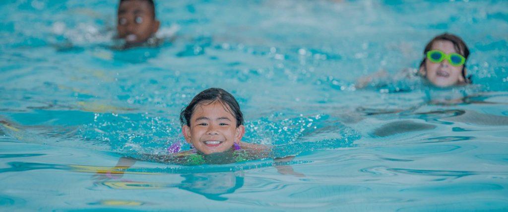 three children swimming in an indoor pool