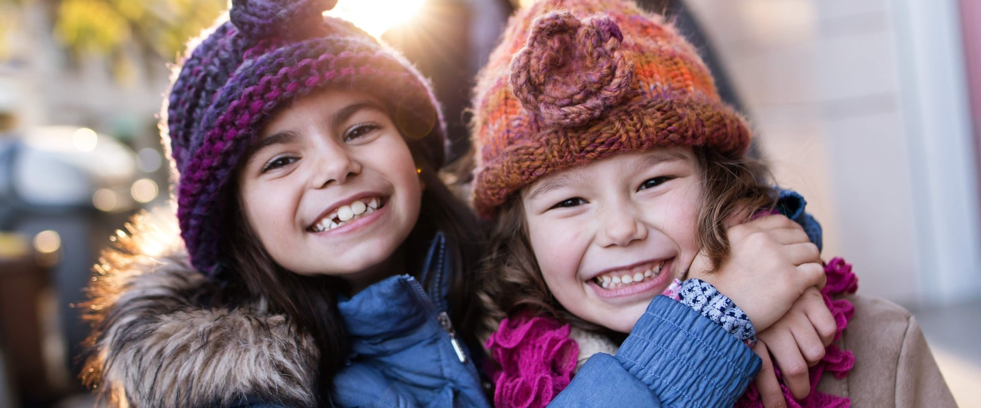 Sisters hugging and smiling at camera in winter on city street