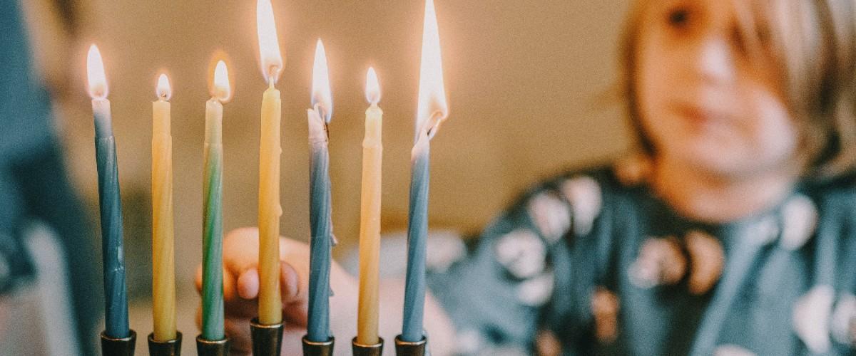 child lighting menorah for Hannukah at home