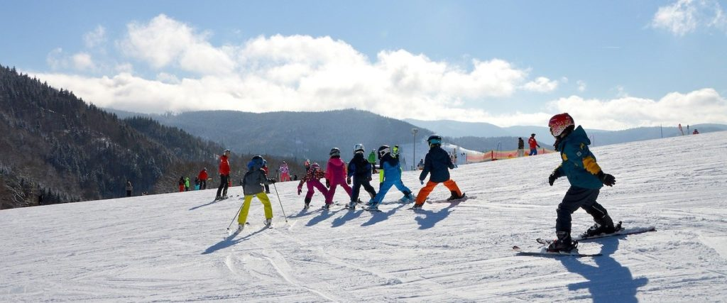 group of young kids getting a ski lesson on a ski hill with instructor