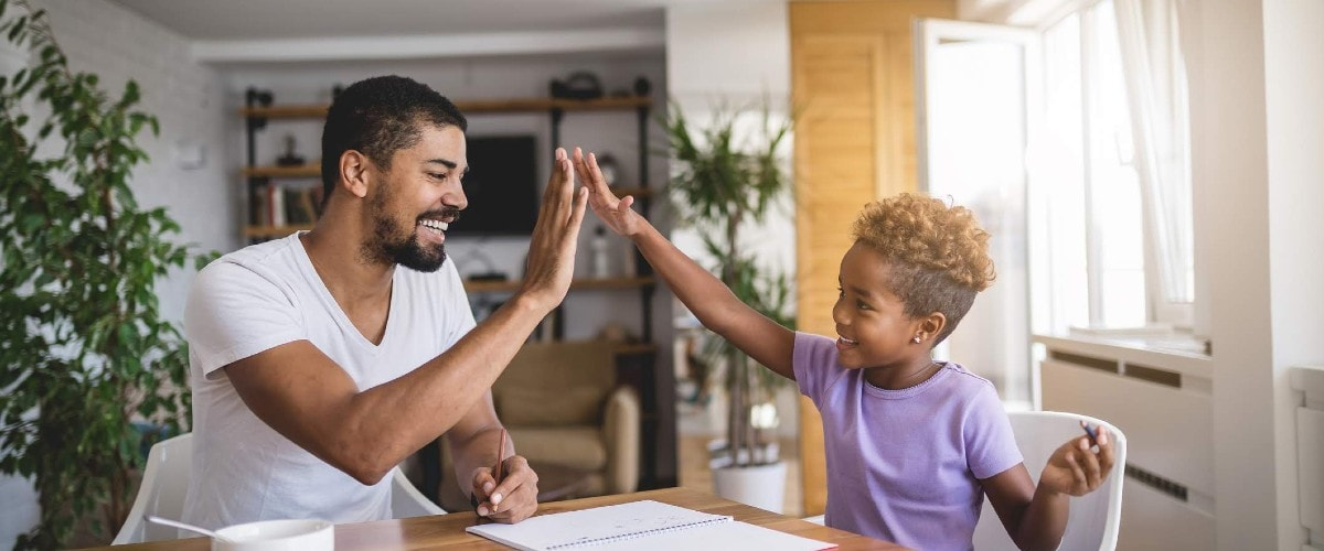 dad and child high-five over kitchen table with homework