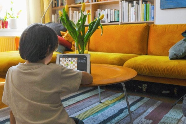 child playing online chess on tablet in living room
