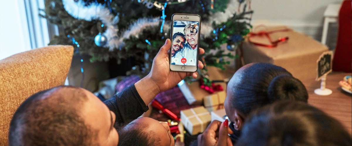 family talking to grandparents on video chat in living room in view of Christmas tree