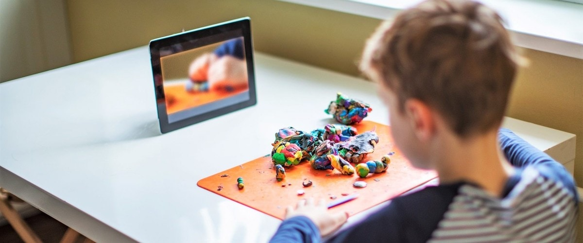child building with clay at home and watching tablet